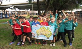 Group of school children hold large map of Australia