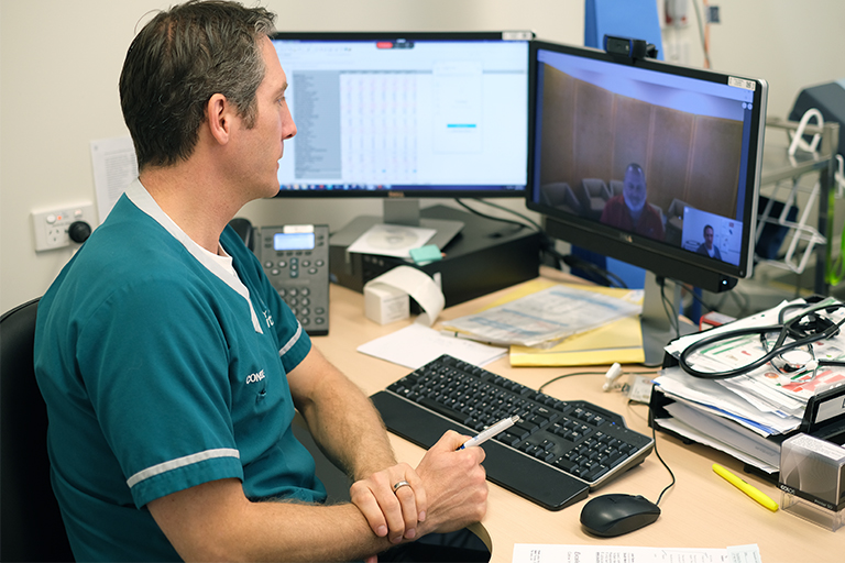 A male health professional sits in front of computer and conducts an online conversation with two other people who are visible on the computer screen.