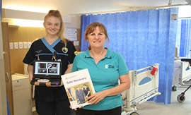 Nurse and physiotherapist holding workbook and portable DVD player