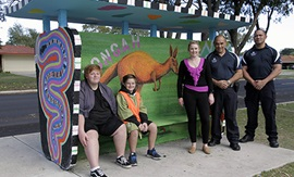 Two high school aged students sit at brightly painted bus stop, with a woman and two men standing nearby. A large kangaroo has been painted on the wall of the bus stop.
