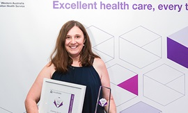 A woman holding a certificate and a trophy stands in front of a banner that reads 'Excellent health care'.