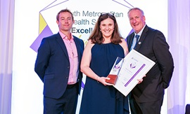 A man and two woman stand in front of a banner that reads South Metropolitan Health Service Excellence Awards. The woman holds a trophy and framed certificate.