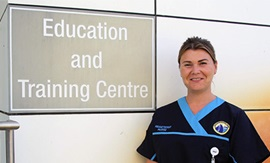 A female registered nurse stands beside a sign that reads Education and Training Centre