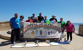 Group of people at beach holding colourful banner reading 'Mental Health Week'