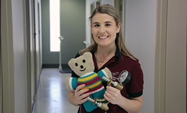 A young female occupational therapist holds a knitted teddy bear.