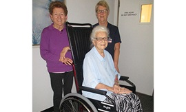 An elderly woman sits in a wheelchair. Behind her stands another woman and a female nurse.