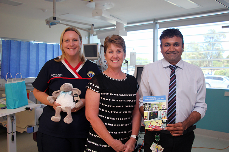 A female nurse standing beside a man and a woman in a treatment room. The nurse is holding a toy sheep.