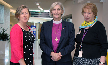 Three women standing in a corridor. The woman in the middle is the Archbishop of Perth.