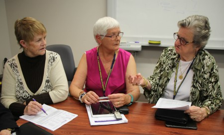 Three women talking at meeting room table