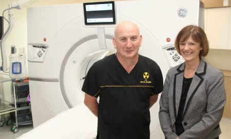Man and woman standing in front of CT scanner