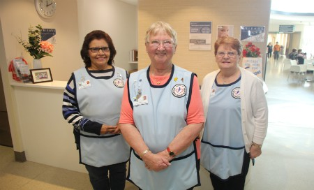 Three women wearing blue aprons standing in front of hospital concierge desk