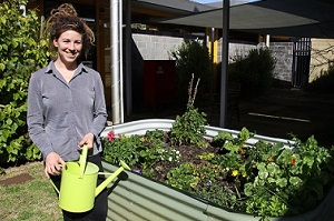 A woman holding a watering can and standing next to a garden bed