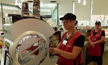A woman making coffee at a hospital kiosk