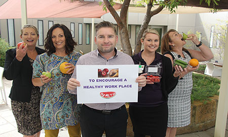 "Group of staff holding fruit and man in the middle holding sign reading ""To encourage a healthier workplace"""