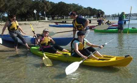 Group of four people in kayaks on beach shore