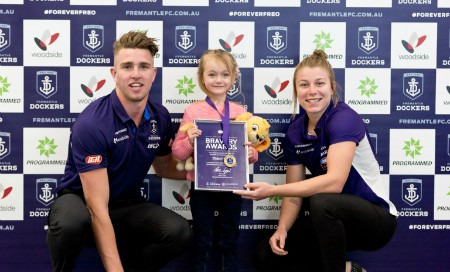 A man and woman in Fremantle Dockers shirt stand beside a small girl holding ceritificate