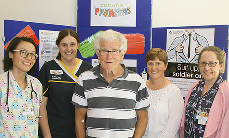 An older male patient stands with four female health professionals