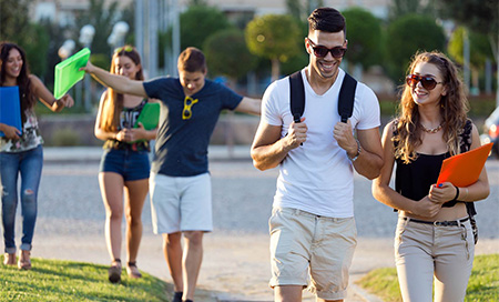 A group of young adults walking in a park